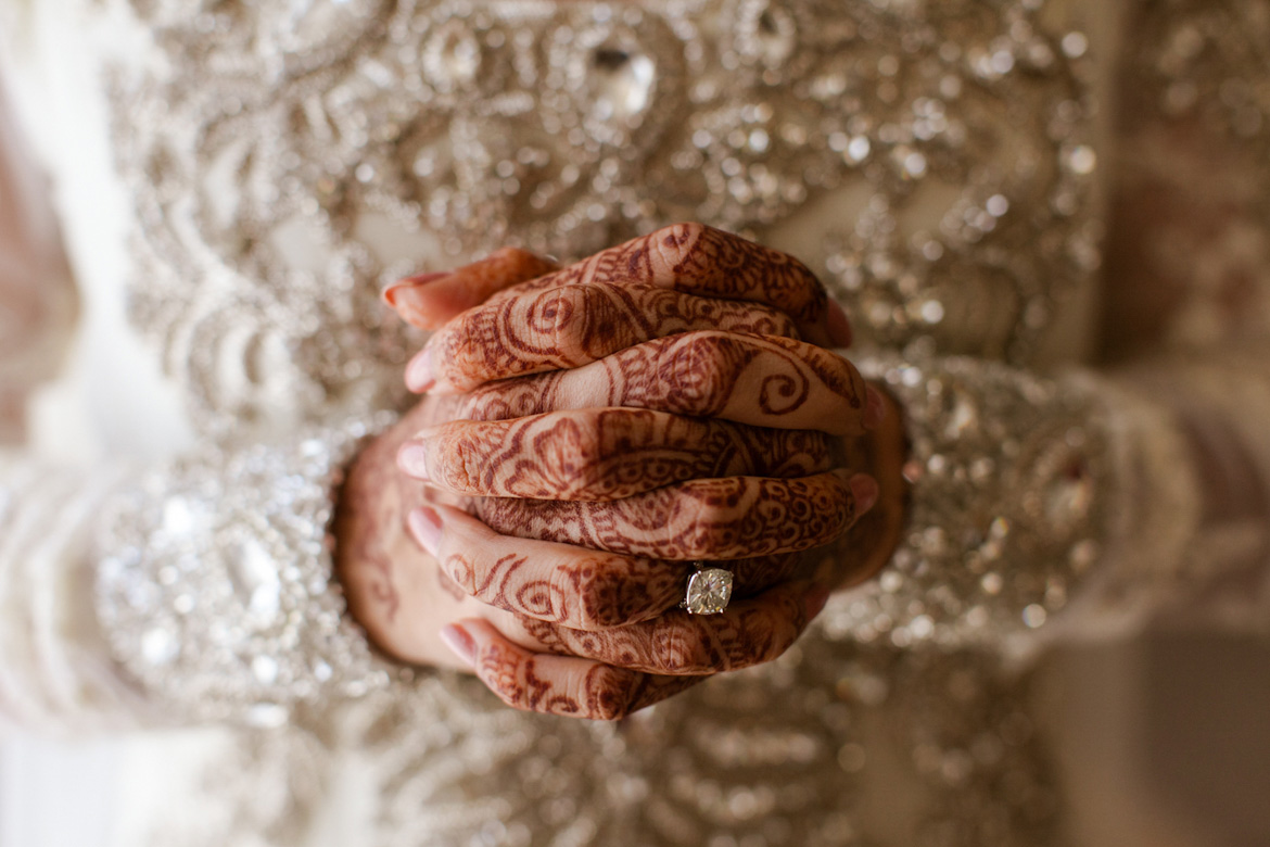 Detail wedding photo of brides ring and henna tattoos