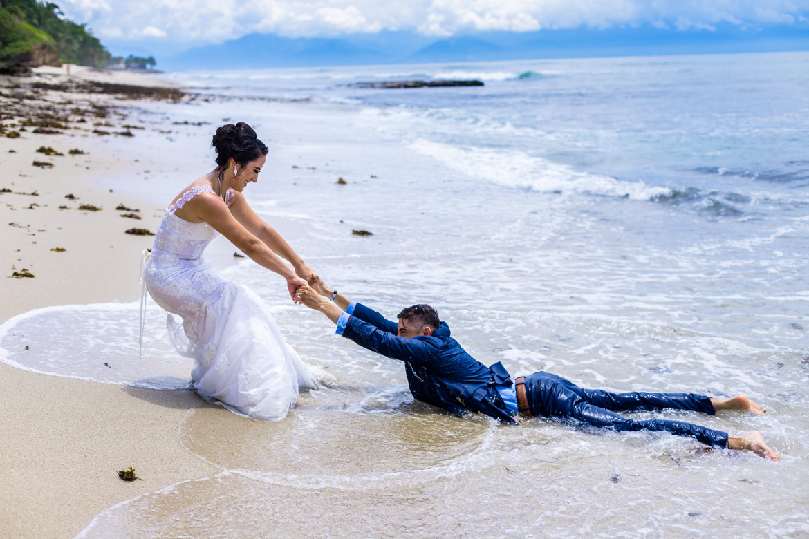 Fun trash the dress photo of bride and groom playing in the water
