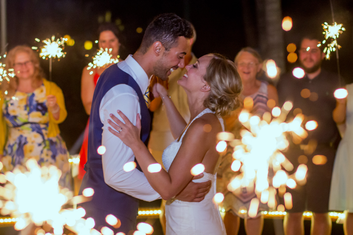Candid photo of bride and groom during first dance surrounded by sparklers at destination wedding