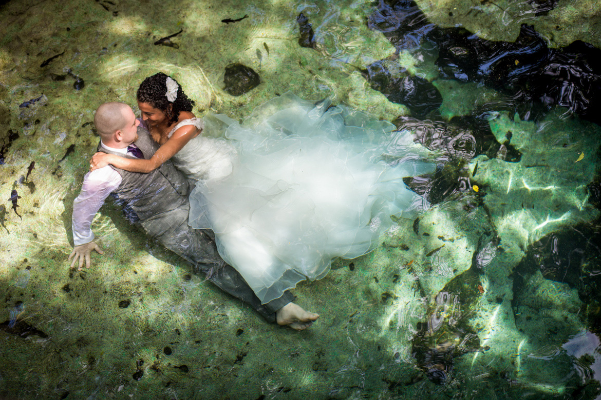 Aerial image of bride and groom in the water during destination wedding trash the dress photo shoot