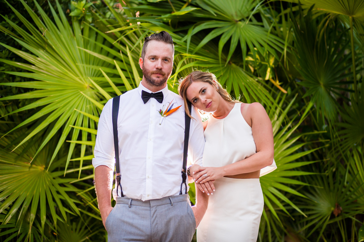 Modern bridal portrait at destination wedding with tropical palm leaf backdrop