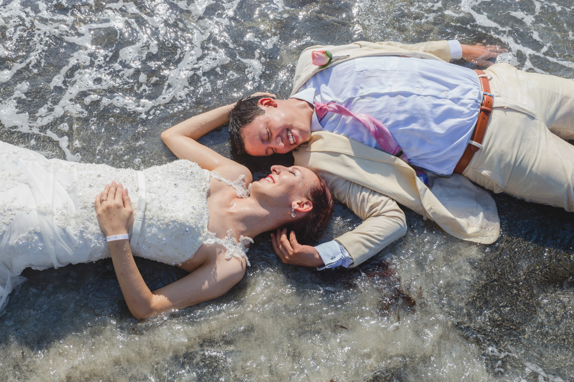 Couple laying on the beach during trash the dress photo session with Adventure Photos