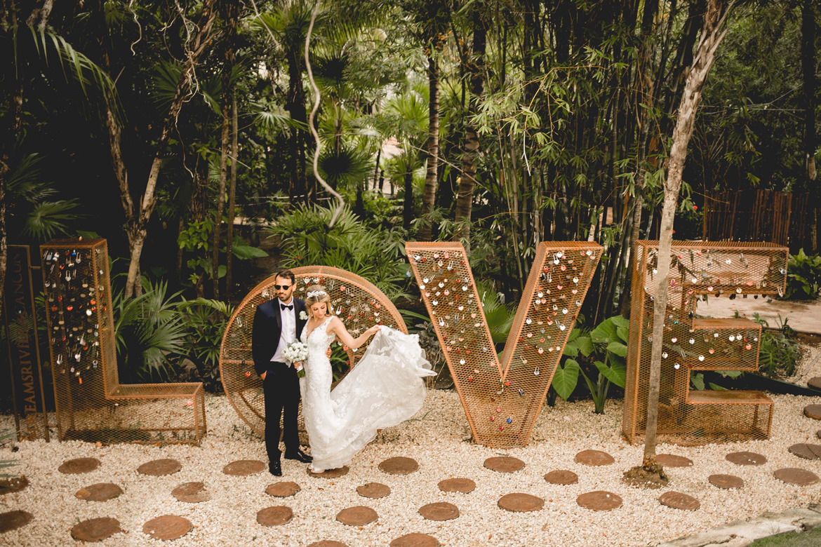 Candid destination wedding photo in front of bohemian love marquis sign on the beach