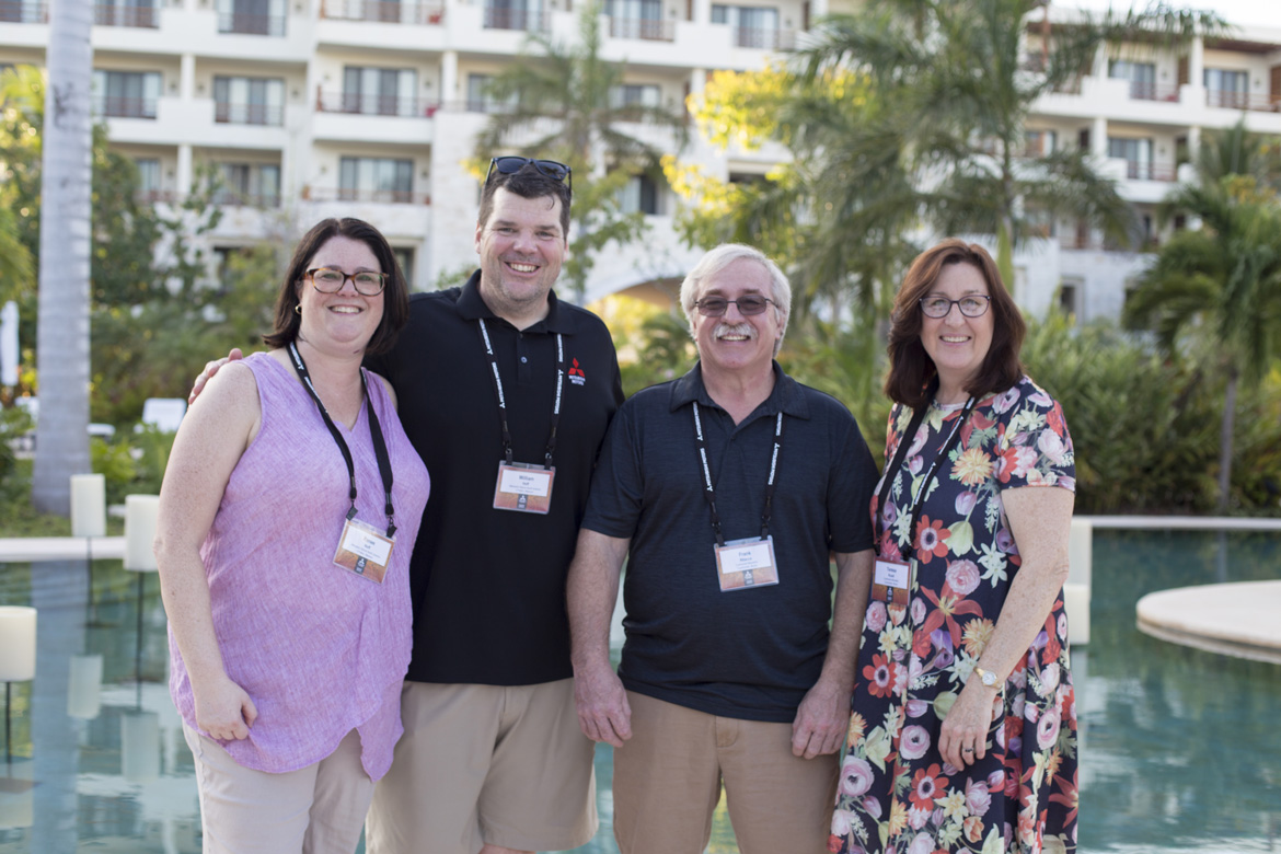 Professional photograph of conference attendees at a tropical resort