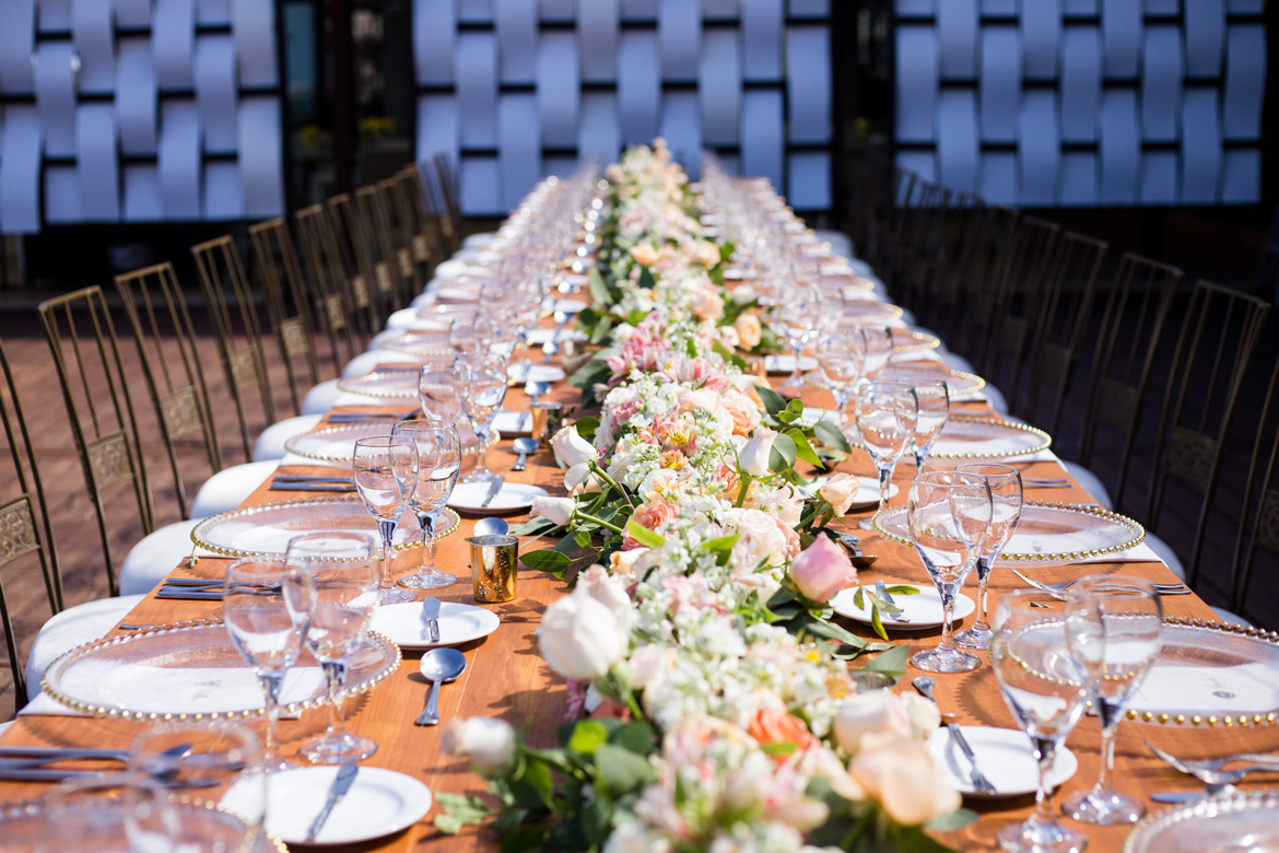 Large king's table styled for marketing photoshoot at resort wedding venue