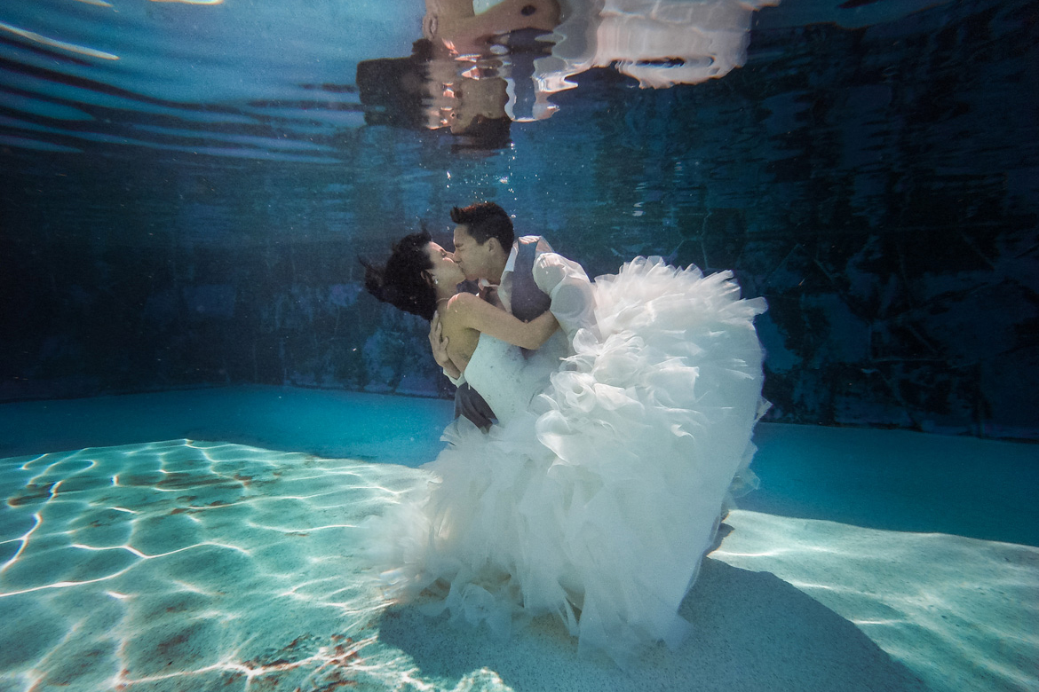 Bride and groom kissing underwater in a pool for trash the dress photo session