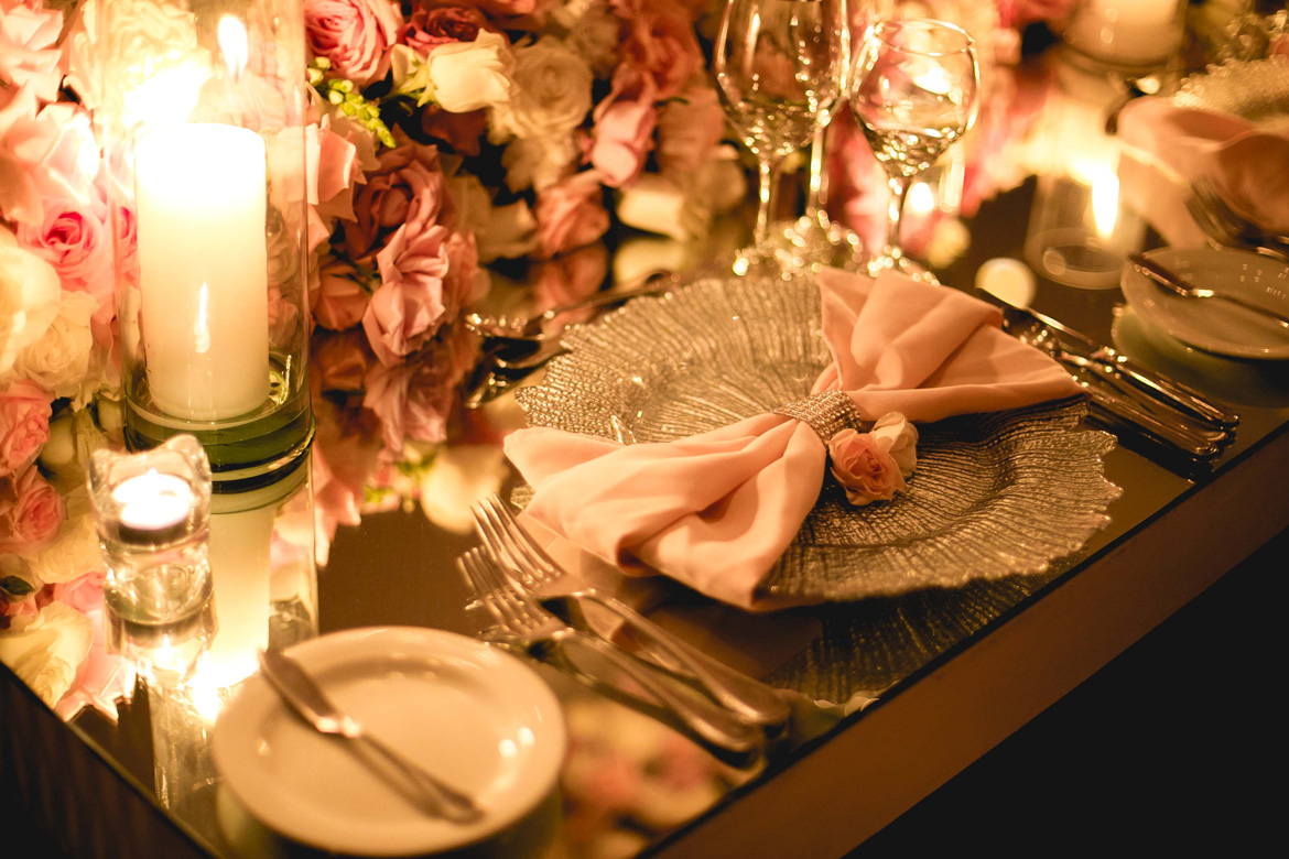 Gold charger plate with pink napkin accent at candlelit harvest table for a destination wedding reception