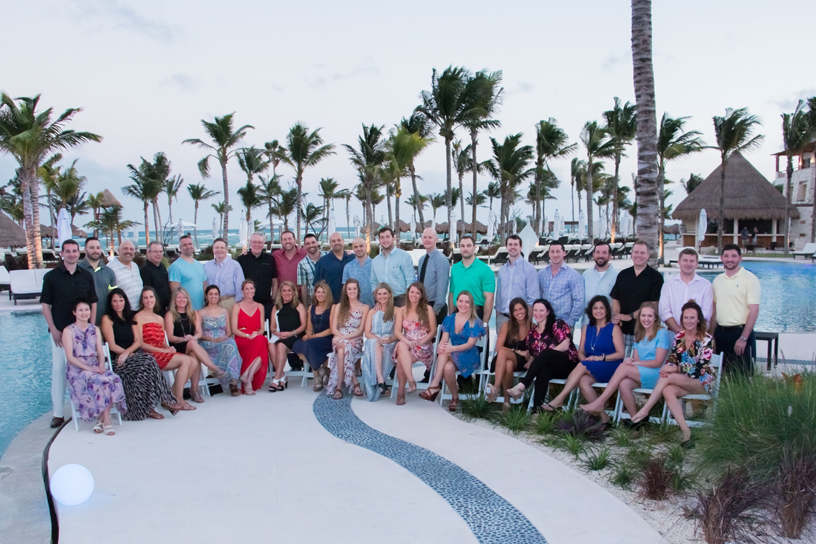 Group photo of employees on incentive trip at a tropical resort