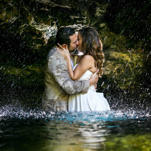 Trash the dress photo of bride and groom kissing in the rain after their destination wedding