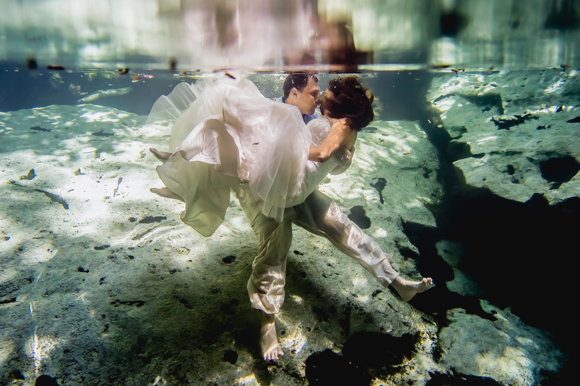 Groom carrying bride underwater for trash the dress photo shoot