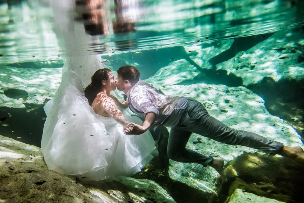 Bride in ball gown kissing groom underwater in tropical trash the dress photo shoot