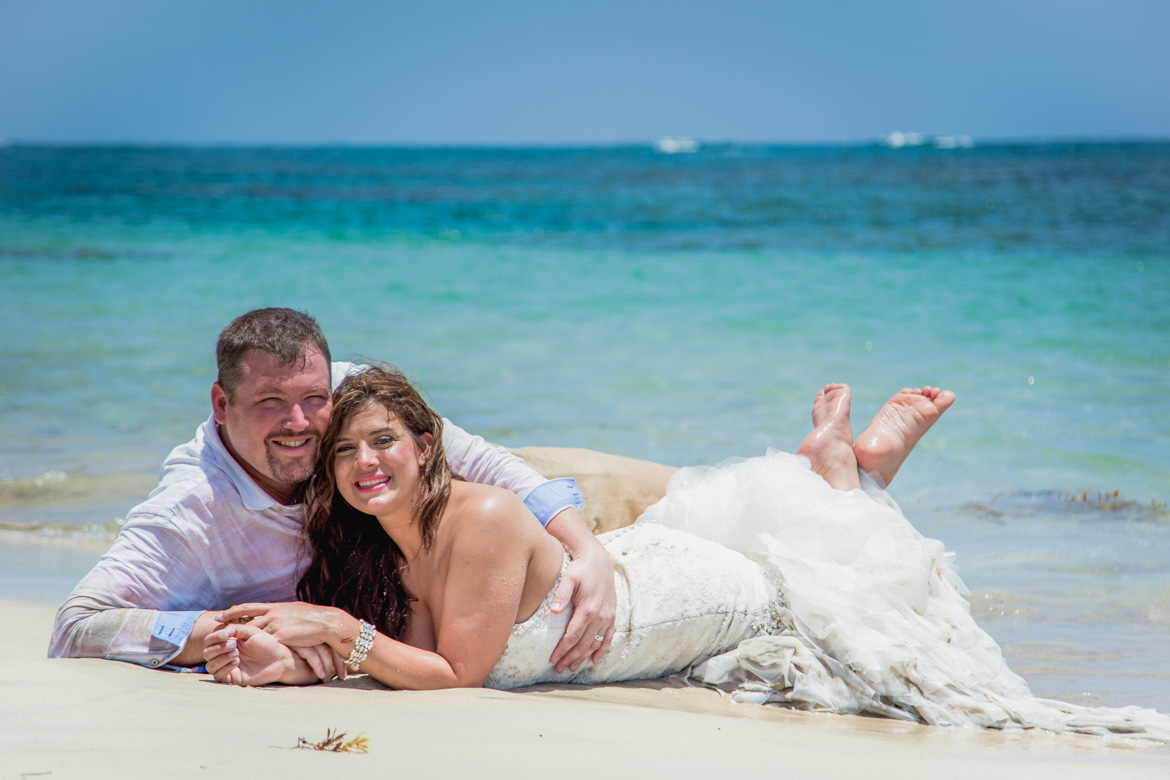 Bride and groom snuggled up on beach for trash the dress photo session