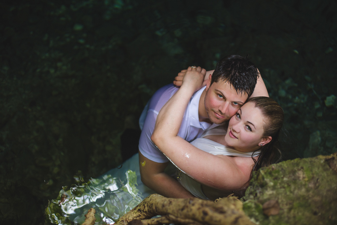 Portrait of bride and groom in a cenote during trash the dress photo session with Adventure Photos