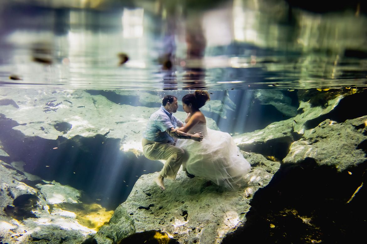 Bride and groom embracing underwater in unique trash the dress wedding photo