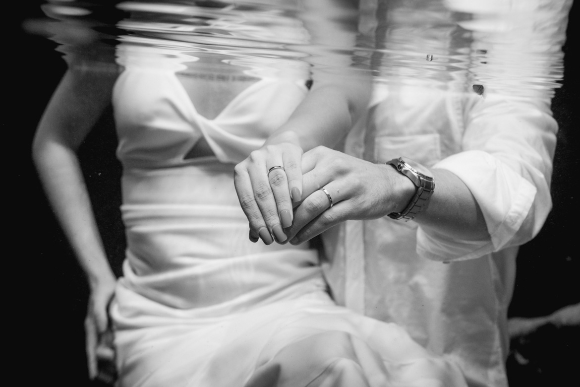 Couple showing off wedding bands during underwater photo shoot with Adventure Photos
