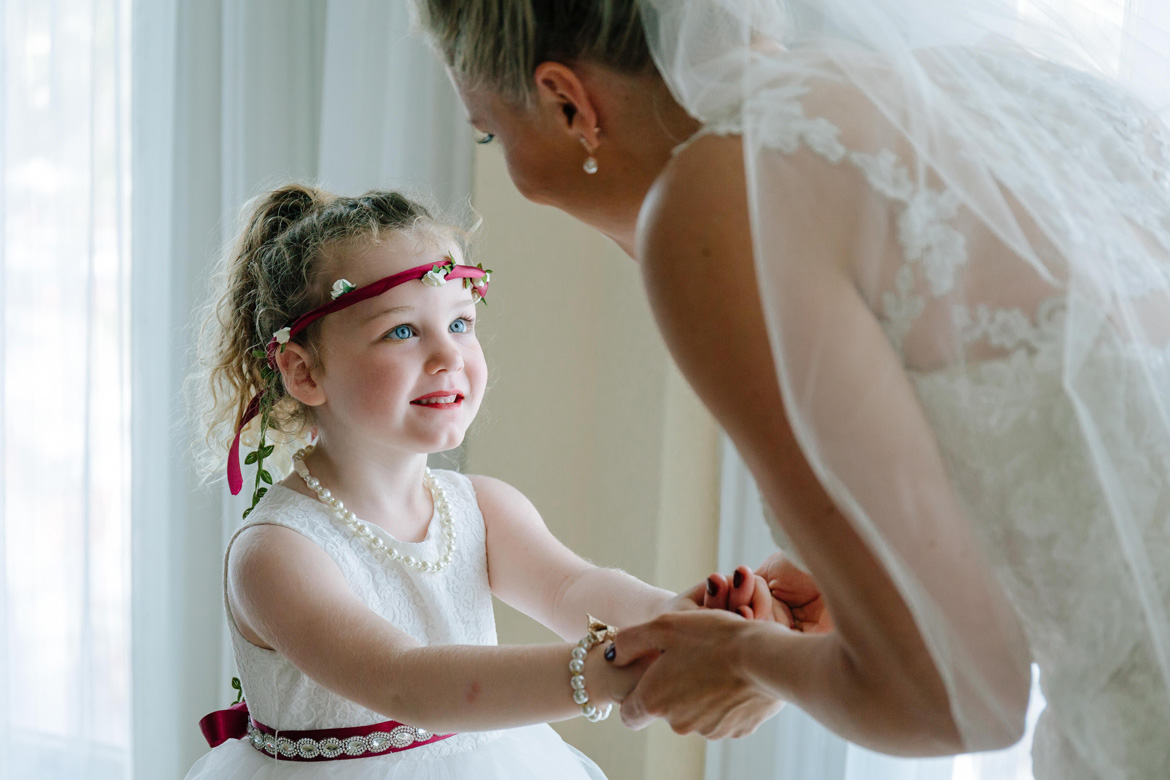 Candid destination wedding photo of bride and flower girl