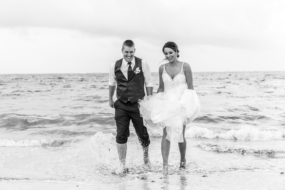 Destination wedding photo of bride and groom in ocean