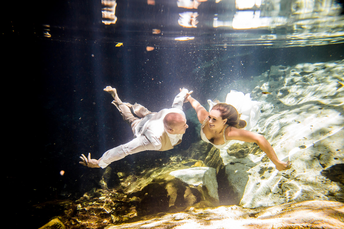 Photo of couple underwater holding hands during trash the dress shoot