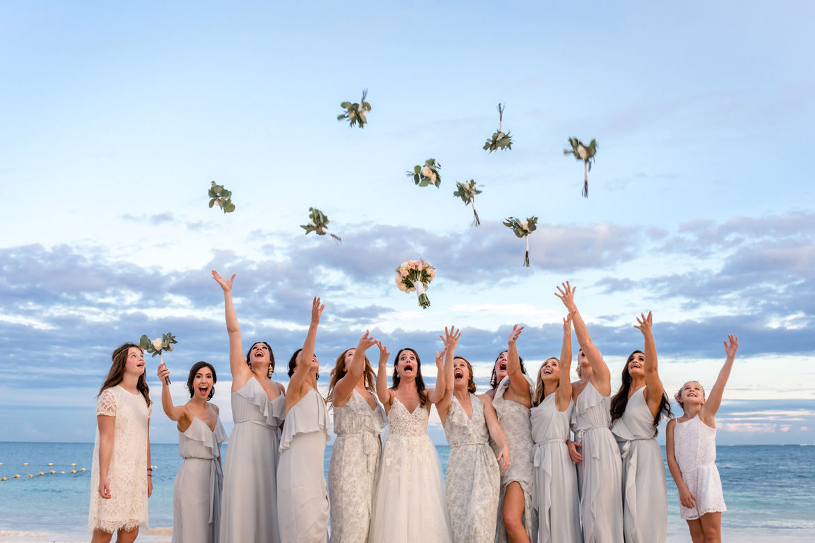 Photo of bride and bridesmaids tossing bouquets at destination wedding on the beach