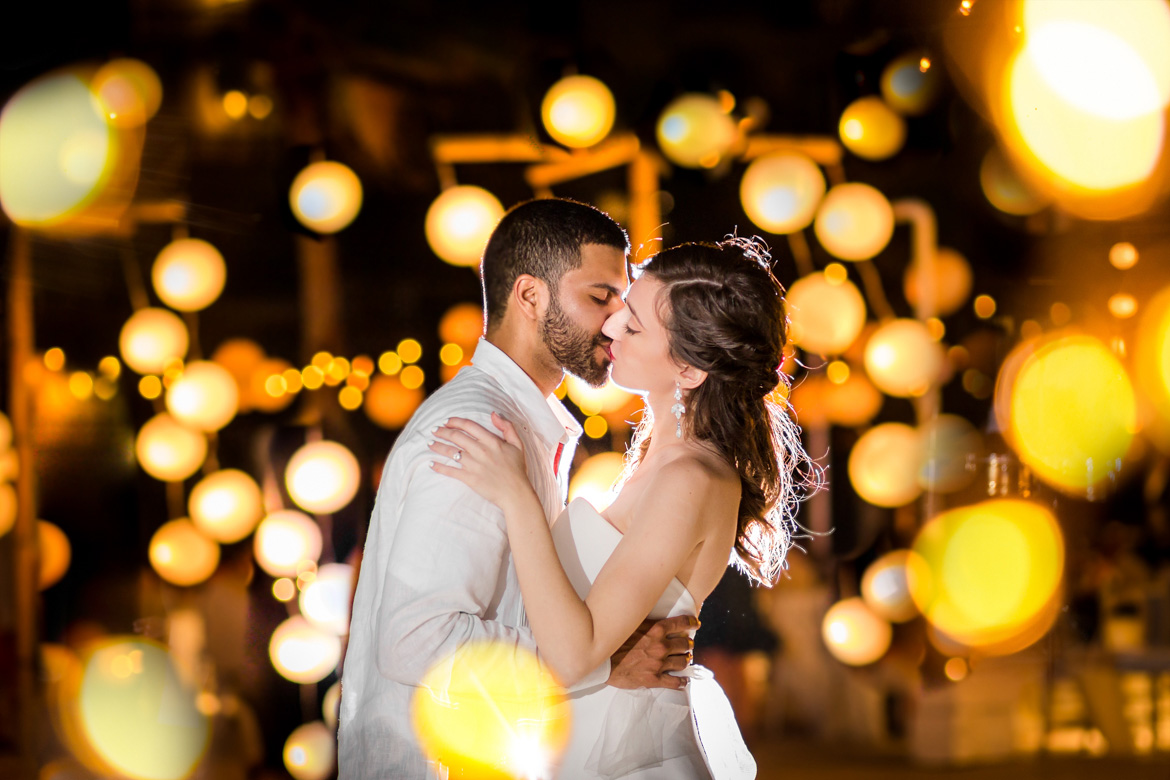 Photo of bride and groom sharing a kiss at nighttime wedding reception lit by fairy lights