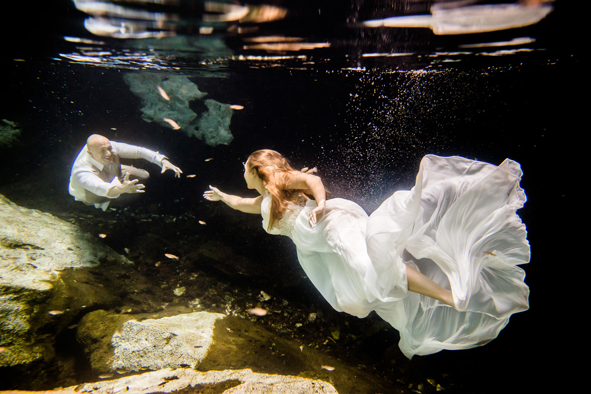 Creative underwater photo of bride and groom during trash the dress photo shoot for destination wedding