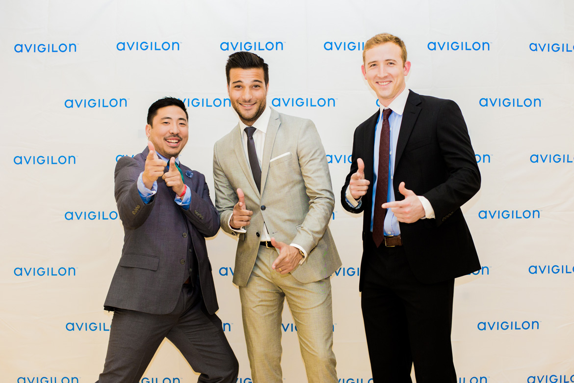 Employees posing in front of social media wall at corporate event captured by professional photographer