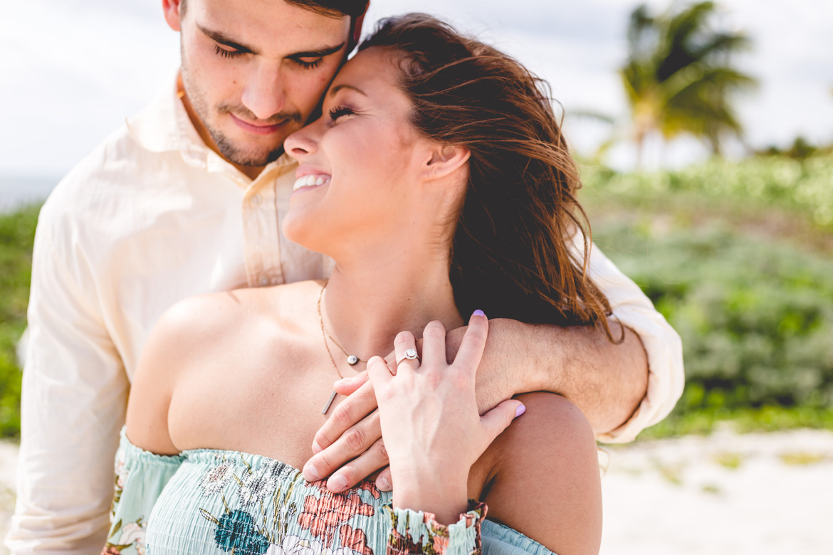 Newly engaged couple smiling on a beach in Puerto Vallarta.