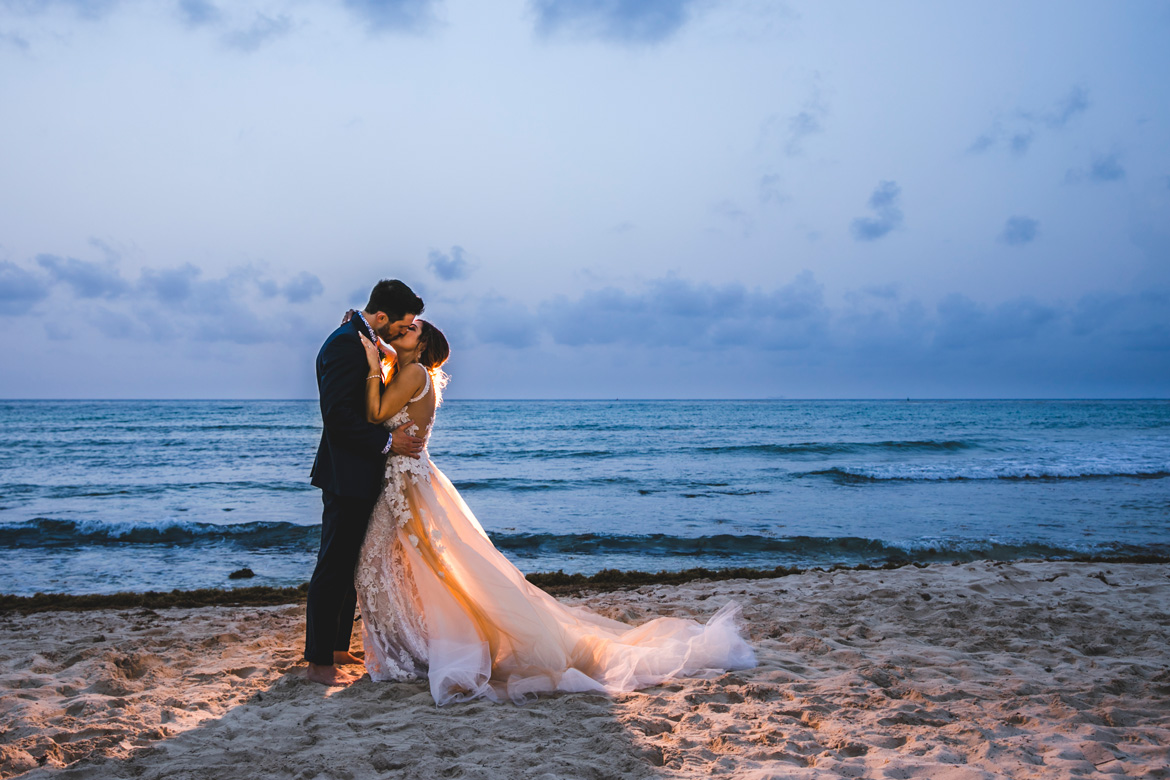Kissing bridal portrait on beach at sunset during destination wedding captured by Adventure Photos