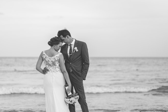 Bride laying her head on grooms shoulder during bridal portrait session on the beach