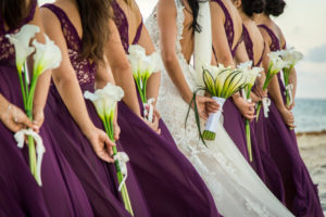 Bridesmaids holding flowers behind back
