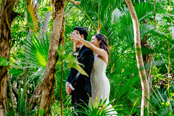Bride covering grooms eyes before first look in at a beautiful tropical wedding