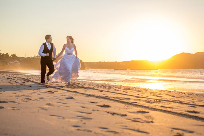 Bride and groom running along beach in candid photo captured by Adventure Photos