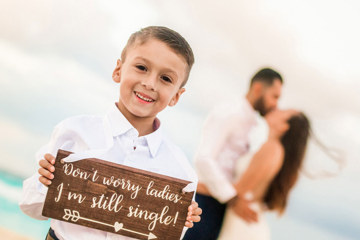 """Image of ring bearer with """"Don't worry ladies I am single"""" sign for a unique wedding photo idea"""
