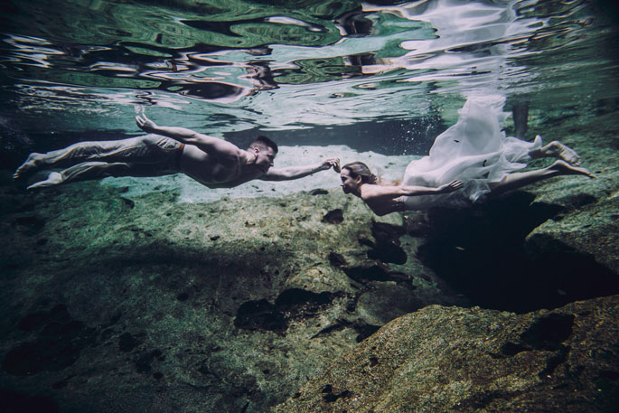 Bride and groom swimming underwater at Cancun trash the dress photo session following their destination wedding