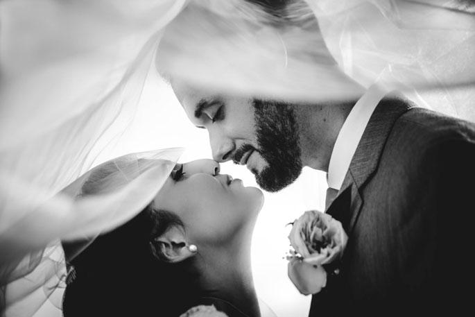 Bridal portrait of couple framed by the brides veils for a unique wedding album image