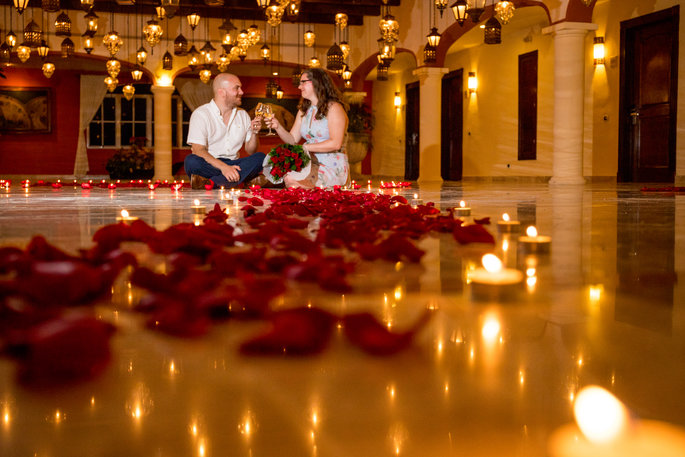 Romantic proposal at resort in ballroom covered with roses and candles captured by Adventure Photos