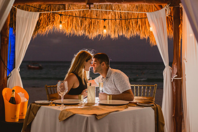 Couple enjoying romantic dinner on the beach during resort vacation captured by Adventure Photos