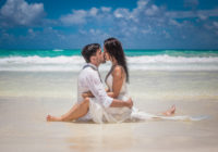 couple kissing on the beach with the waves washing over them