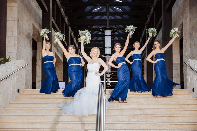Bride and her bridesmaids posing on stairway