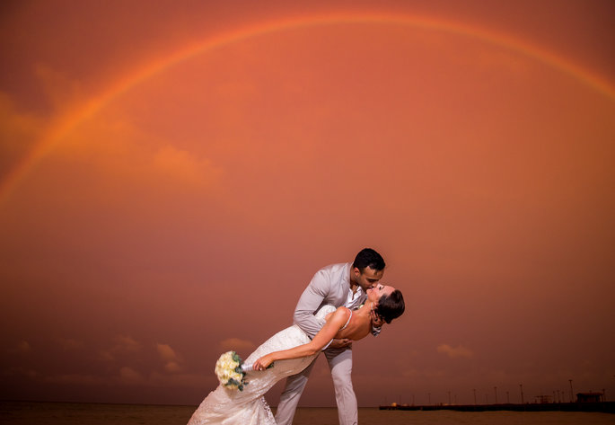 couple on their wedding day kissing with a beautiful sunset behind them
