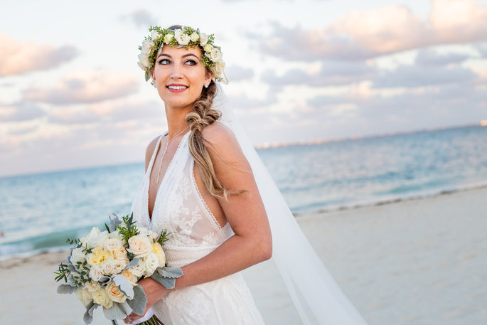 bride smiling at the camera on the beach holding flowers