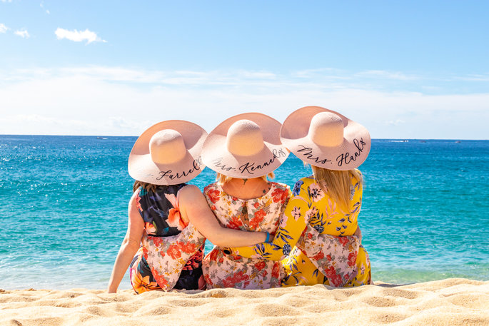 Three friends wearing hats on the beach facing the ocean