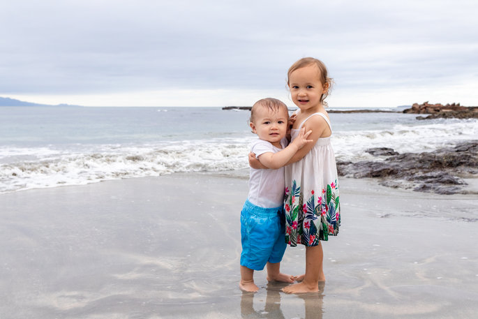 Cute young brother and sister embracing on the beach