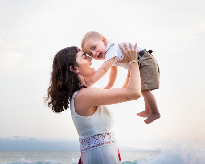 mother playing with her baby boy on the beach