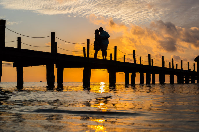 sunset photo of a couple kissing on a dock