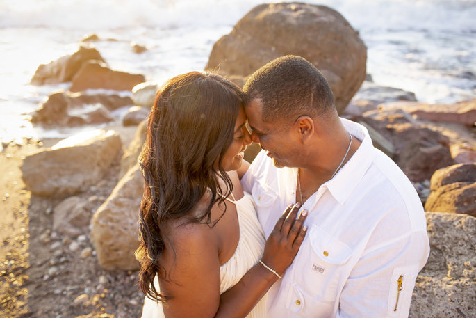 couple touching noses on the beach for wedding photos
