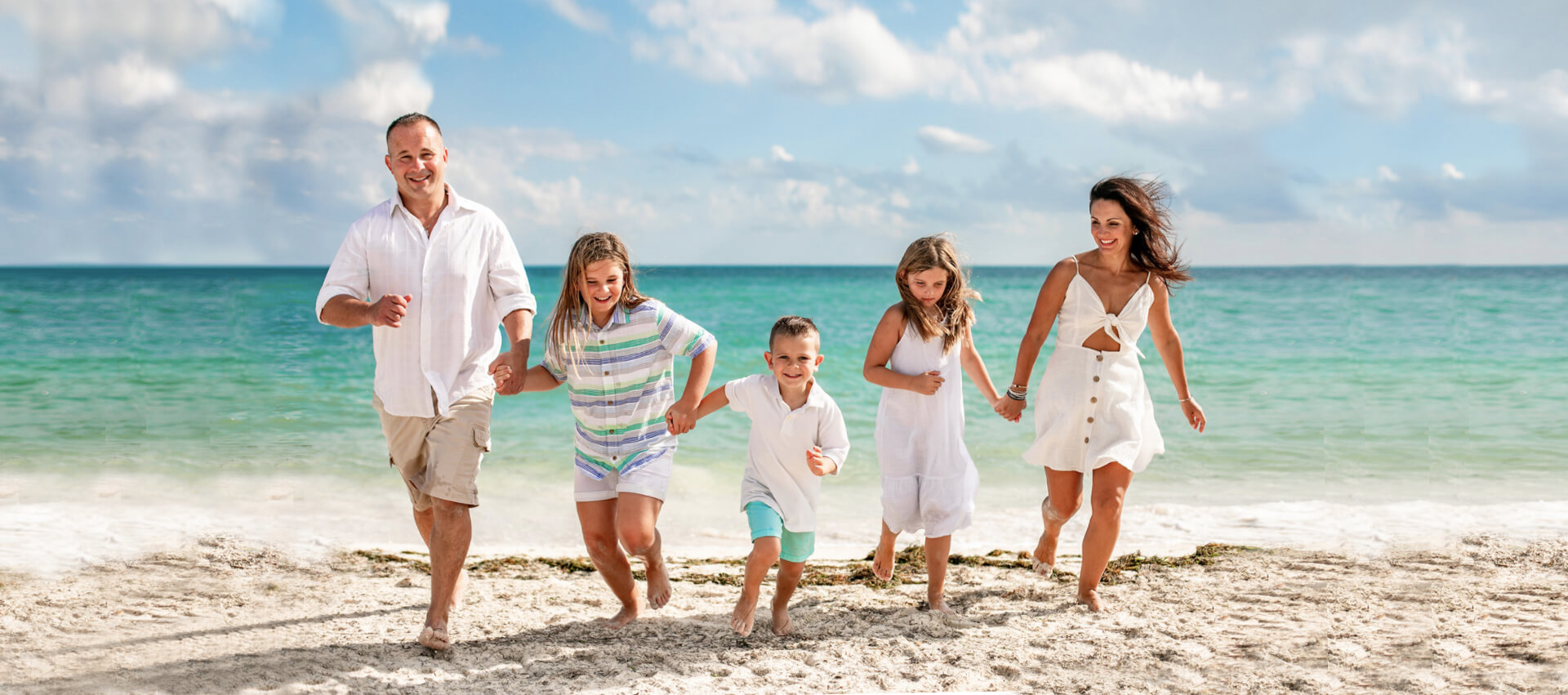 Portrait of a family holding hands while running toward the camera on the beach.