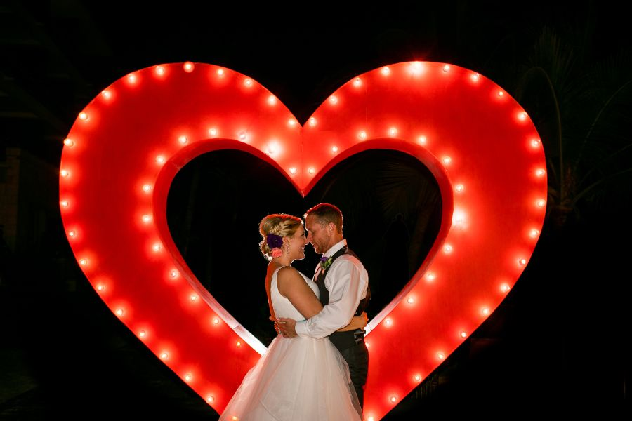 Posed Artistic Wedding Photo in Front of Neon Heart Sign by Adventure Photos