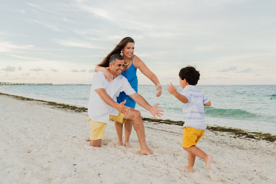 Son Running to Mother and Father on Resort Beach in Lifestyle Photoshoot by Adventure Photos