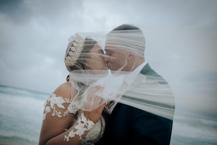 Close up of bride and groom with veil blowing in the wind during bridal portrait session with Adventure Photos